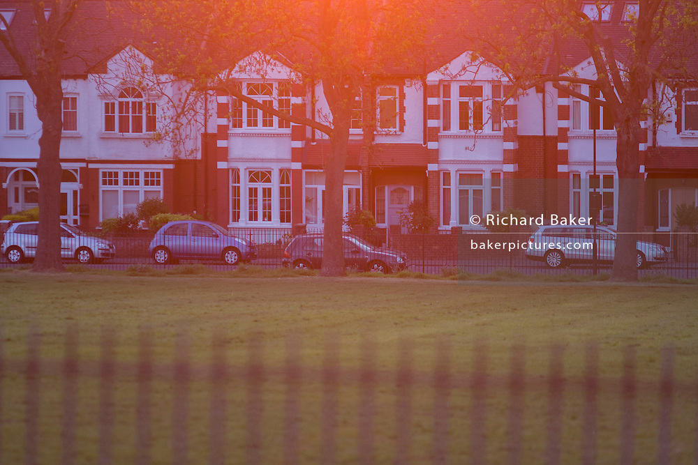 Setting sun turns orange behind Edwardian period homes in south London park.