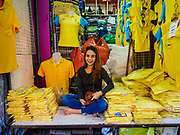 "03 JULY 2018 - BANGKOK, THAILAND: A vender in Bobae Market in Bangkok sells yellow shirts that save ""Long Live the King."" The birthday of King Maha Vajiralongkorn Bodindradebayavarangkun, Rama X, is 28 July. The King, the only son of Thailand's late King Bhumibol Adulyadej, became the King of Thailand in 2016 after the death of his father. King Vajiralongkorn was born on 28 July 1952, a Monday. In Thai culture each day of the week has a color, and yellow is the color is associated with Monday, so people wear yellow for the month before his birthday to honor His Majesty.    PHOTO BY JACK KURTZ"