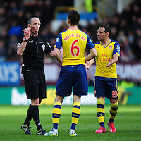 Referee Mike Dean speaks to Arsenal's Laurent Koscielny, centre, as Arsenal's Santi Cazorla, right, tries to have his say<br /> <br /> Photographer Chris Vaughan/CameraSport<br /> <br /> Football - Barclays Premiership - Burnley v  Arsenal - Saturday 11th April 2015 - Turf Moor - Burnley<br /> <br /> © CameraSport - 43 Linden Ave. Countesthorpe. Leicester. England. LE8 5PG - Tel: +44 (0) 116 277 4147 - admin@camerasport.com - www.camerasport.com