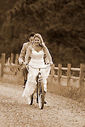 Bride and groom riding a tandem bicycle on their wedding day in Oregon's Wallowa Valley.