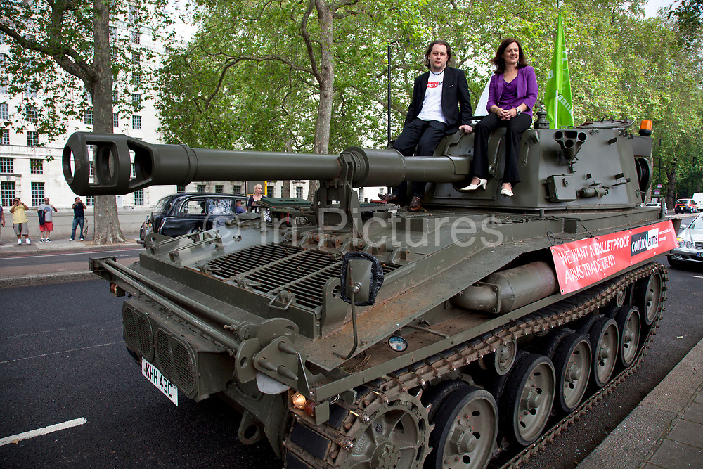 Spokespeople Anna Macdonald and Oliver Sprague sit atop the tank. Campaigners and supporters from Oxfam and Amnesty International, as part of the Control Arms coalition, drive an Abbot gun tank around central London to highlight the need for a global Arms Trade Treaty (ATT) to be agreed during a United Nations conference next month (July 2012). London, England, UK. 27th June 2012.