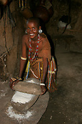 Datoga woman in traditional leather dress adorned with beads and brass bracelets milling grain to flour.