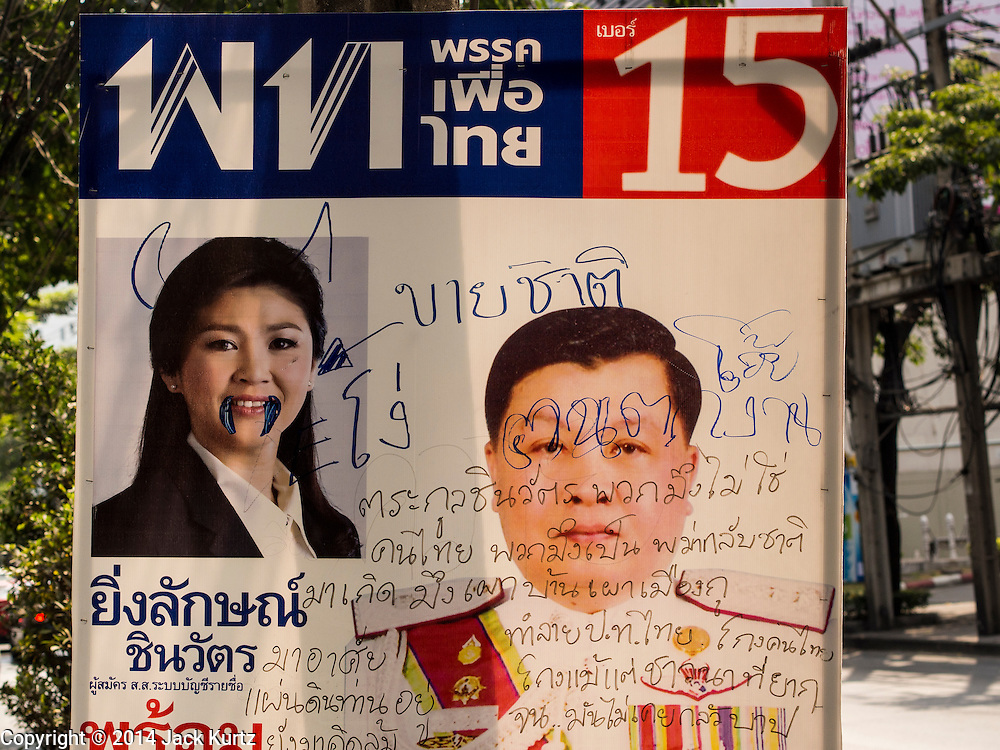 29 JANUARY 2014 - BANGKOK, THAILAND: A defaced campaign sign for the ruling Pheu Thai party on Soi 63 Sukhumvit (Ekkamai) in Bangkok. Thais are supposed to vote Sunday, February 2 in a controversial national election. Anti-government protestors have vowed to disrupt the election. One person was killed and several injured in election related violence during early voting on Sunday Jan. 25. The ruling Pheu Thai party is widely expected to win the election, which is being boycotted by the Democrats and opposition parties.      PHOTO BY JACK KURTZ