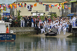 © Licensed to London News Pictures. 01/05/2017 May Day celebrations in Padstow Cornwall.The Bluer Oss. Drinks from Padstow Harbour.  The Blue Oss and the Red Osds lead the traditional May Day celebrations around the historic harbour of Padstow in Cornwall.<br /> Despite the rain large crowds attended the annual event.Photo credit : MARK HEMSWORTH/LNP