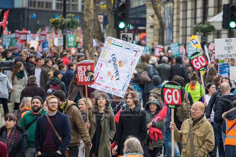 """London, April 16th 2016. A protester's banner proclaims the """"monopoly"""" of the government's policies as thousands of people supported by trade unions and other rights organisations demonstrate against the policies of the Tory government, including austerity and perceived favouring of """"the rich"""" over """"the poor""""."""