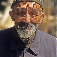 An elderly Uygur man walks a wooded lane near Kashgar (Kashi), a town on the ancient Silk Road in Xinjiang, China.  His hat identifies him as a Muslim and perhaps because of that the Uygur people are widely oppressed in China - almost to the extent of the Tibetans.