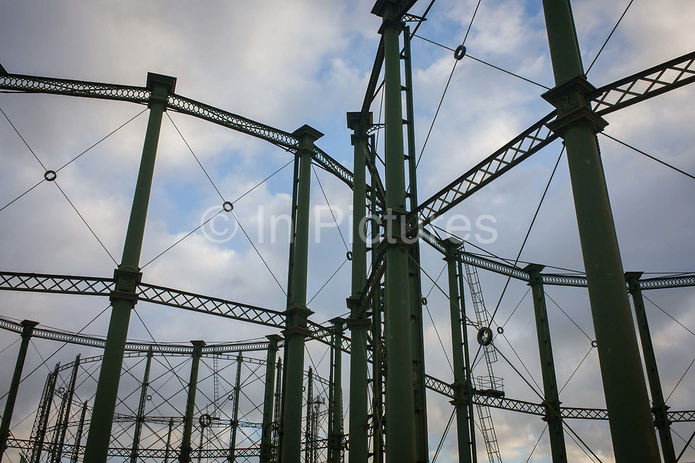 Empty rigid-design gas holders architecture at the Oval, South London. The steel frames are seen against an afternoon sky at Oval, in south London - their strengthening architecture showing how the gasometer design has been an effective method storing gas for a hundred years. The Oval Gasholders at The Oval cricket ground, in spite of no longer being used, are now a grade 2 listed structure. Typical volumes for large gasholders are about 50,000 cubic metres, with 60 metre diameter structures. Gasholders tend to be used nowadays for balancing purposes (making sure gas pipes can be operated within a safe range of pressures) rather than for actually storing gas for later use.