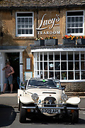 Vintage car outside the tearoom in Stow on the Wold in The Cotswolds, United Kingdom. Stow-on-the-Wold is a small market town and civil parish in Gloucestershire, England. The town was founded as a planned market place by Norman lords, to take advantage of trade on the converging roads. The Cotswolds is an area in south central England. The area is defined by the bedrock of limestone that is quarried for the golden coloured Cotswold stone. It contains unique features derived from the use of this mineral; the predominantly rural landscape contains stone-built villages and historical towns.
