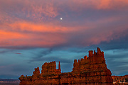 Approaching storm clouds, turned red by the setting sun, frame the moon as it rises over a large hoodoo in Bryce Canyon National Park, Utah. Hoodoos are remanants of large sandstone fins that have been subjected to centuries of erosion.