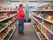 "25 FEBRUARY 2020 - BUTTERFIELD, MINNESOTA: CONNIE BRAATEN, who has lived in Butterfield since 2003, walks through the grocery section at the True Value Hardware Store in Butterfield. She used to shop in St. James, MN, about 10 miles away. Butterfield is a farming community of about 500 people 130 miles southwest of the Twin Cities. The town has been a ""food desert"" for 10 years after its only grocery store closed in 2010. Barb Mathistad Warner and Mark Warner purchased the True Value store in Butterfield in December, 2018 and started selling groceries in the store in May, 2019. For residents of Butterfield going to a grocery store meant driving 10 miles to St. James, MN, or 20 miles to Windom, MN, the two nearest communities with grocery stores. The USDA defines rural food deserts as having at least 500 people in a census tract living 10 miles from a large grocery store or supermarket. There is a convenience store in Butterfield, but it sells mostly heavily processed, unhealthy snack foods that are high in fat, sugar, and salt.   PHOTO BY JACK KURTZ"