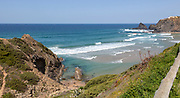 Atlantic Ocean waves breaking on rocky headland and bay with sandy beach, Praia de Odeceixe, Algarve, Portugal, Southern Europe