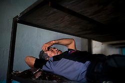 Men pass the time in a cheap guesthouse in Altar, Sonora, while they wait to illegally cross the border.  Altar is the starting point for many migrants' journeys to the US. In Altar they find guides and coyotes to take them across the border.  The town's economy is nearly entirely dependent on the migrants. Recently drug cartels have become involced in the smuggling of people, using the same routes as the drugs and charging the migrants an exit tax to leave the country.