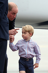 Prince George holding the hand of his father, the Duke of Cambridge, as he arrives at Warsaw's Chopin Airport with the Duchess of Cambridge and Princess Charlotte for the start of their five-day tour of Poland and Germany.