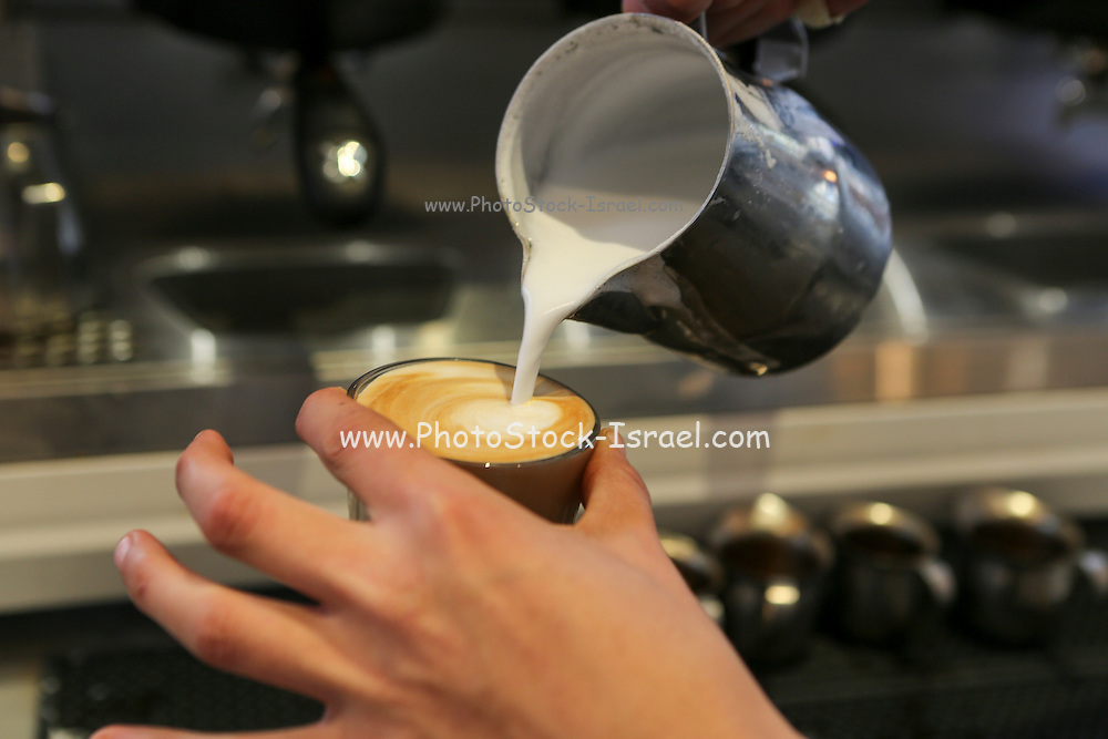 Hands of a Barista as he prepares a cup of cappuccino