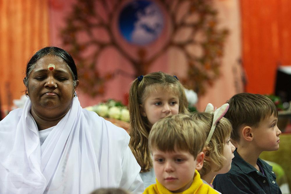 Voor de darshan mediteert Amma, omringd door kinderen. In de Expo in Houten is Mata Amritanandamayi, beter bekend als Amma of 'hugging mother', aanwezig om mensen te omhelzen en te inspireren. Het driedaags benefiet in Houten is het grootste spirituele festival in Nederland en zal naar verwachting 15.000 bezoekers trekken.<br /> <br /> Before she starts with the darshan Amma is meditating, surrounded by children. In the Expo in Houten people are gathering to get a darshan, or hug, by  Mata Amritanandamayi, also known as Amma or 'hugging mother'. Amma is travelling through the world to hug people for inspiring them to make a better world. Amma is one of the twelve most influence spiritual leaders of the world. The event in Houten lasts for three days and is the biggest spiritual event of The Netherlands.