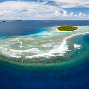 This is an aerial panorama of Fonua'one'one Island in the Vava'u island group of the Kingdom of Tonga. The island and white sand beach visible from a boat at sea level represents only a small fraction of the entire coral reef structure, as is apparent from this aerial view.