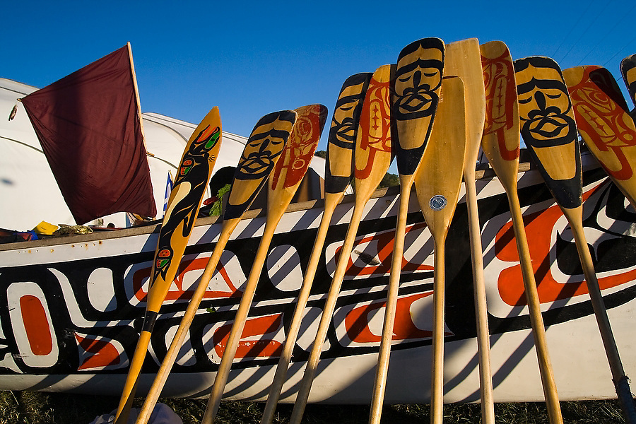 "Paddles rest against Hawaiian-Alaskan Chief Frank Nelson's ornately decorated family canoe at Stommish Beach on the Lummi Indian Reservation, Washington on July 30, 2007.  A crew paddled the canoe all the way from the North end of Vancouver Island to visit the Lummi Nation, hosts of the 2007 Canoe Journey. When in use, the orientation of the paddles reflects the intentions of the crew - the black sides symbolize peace, while the red sides symbolize war. Dancing, singing and ""potlatching"" followed for a week until the canoes left for their return voyage on August 5."