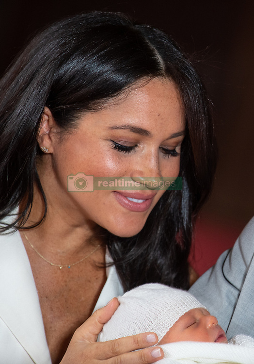 The Duchess of Sussex looks at her baby son, who was born on Monday morning, during a photocall in St George's Hall at Windsor Castle in Berkshire.