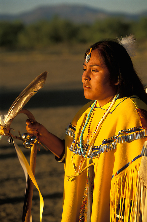 An Apache girl dressed in buckskin dress dances at her Sunrise Dance, a first menstruation rite on the San Carlos Apache Indian Reservation in Arizona, USA. The girl holds a cane that symbolises longevity. The Sunrise Dance is supposed to prepare the girl for adulthood and to give her a long and healthy life without material wants.The ceremony is also an enactment of the Apache creation myth and during the rites the girl 'becomes' Changing Woman, a mythical female figure, and comes into possession of her healing powers.