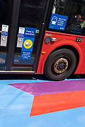 A Covid pandemic face mask sign is on the side of a London bus as it passes over the multi-coloured markings of a crossing at Lower Regent Street, on 16th July 2021, in London, England. Days before the UK governments widespread re-opening of Covid pandamic restrictions Monday 19th July aka Freedom Day, the number of daily infections has risen to 50,000.