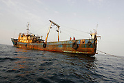 """Chinese Zombie Ships off the coast of West Africa, March-April 2006. These ships are engaged in IUU - illegal, unreported and unregulated fishing off the coast of Guinea, West Africa. The ships themselves have not been in port for perhaps ten years - they crew don't see land for up to two years. The Greenpeace ship Esperanza, with Greenpeace, Environmental Justice Foundation and Guinean authorities participated in the arrest of one of these vessels - on board were boxes for a ship of another name, and with the words """"product of Spain"""". The crewmen, who are essentially indentured labourers live in appalling conditions on board. Some of the vessels no longer function, and are left at anchor offshore, with a skeleton crew on board. Later on the expedition, the Esperanza caught some of the working vessels transhipping boxes to a Korean 'reefer', which it then pursued to Las Palmas, in the Canary Islands. Activists blocked the ship's cranes in for many days over Easter 2006, leading to the seizing of 11,000 boxes fishing stolen from the waters of West Africa and destined for the European market. The fish was returned to Guinea."""