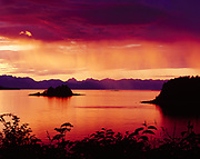 Virga falling beyond Cohen Island with sunset over Favorite Channel, Tee Harbor, Southeast Alaska north of Juneau, Alaska.