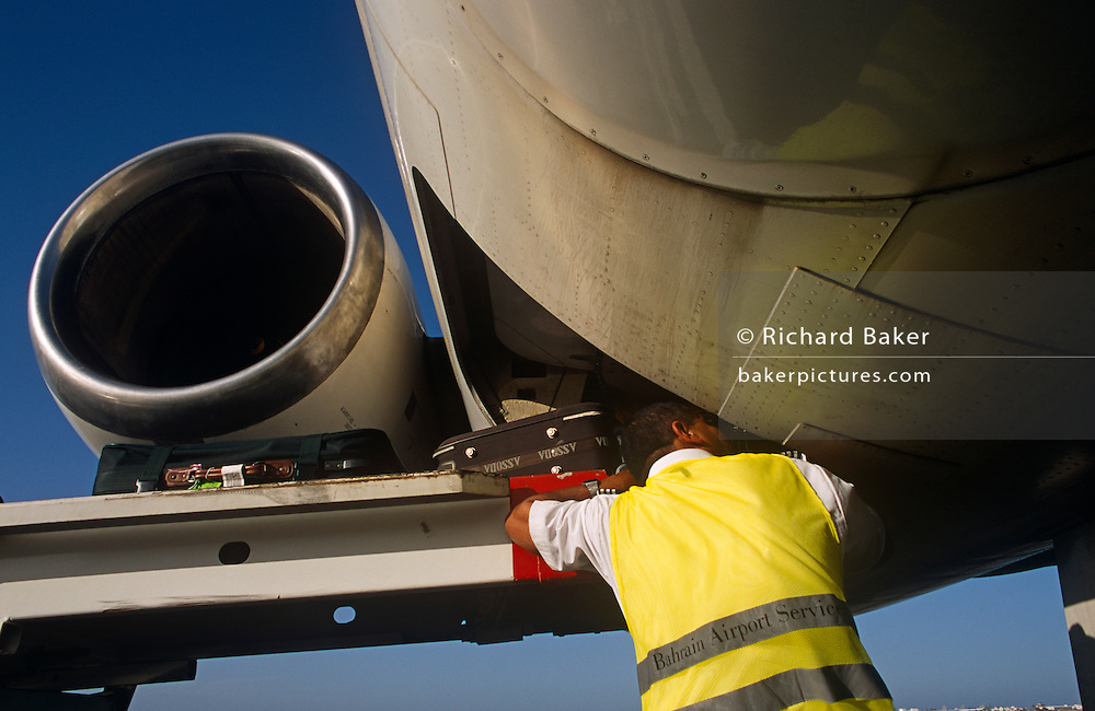 A Bahrani baggage-handler employed by SABTCO loads baggage onto a Saudi Airlines McDonnell-Douglas MD90-30 (registered as HZ-APP) on the apron at the Gulf state of Bahrain's international airport.