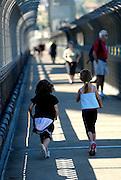 Two children (6 years old) running across the Sydney Harbour Bridge. Sydney, Australia