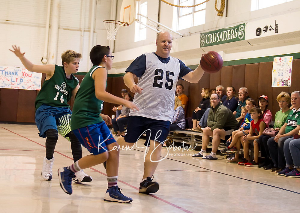 Chris Noyes gets double coverage by Adam Barton and Carter Lloyd during the community basketball game with Holy Trinity students taking on the Laconia Police Dept on Saturday morning.  (Karen Bobotas/for the Laconia Daily Sun)
