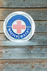 Lifeguard sign hanging wooden shed
