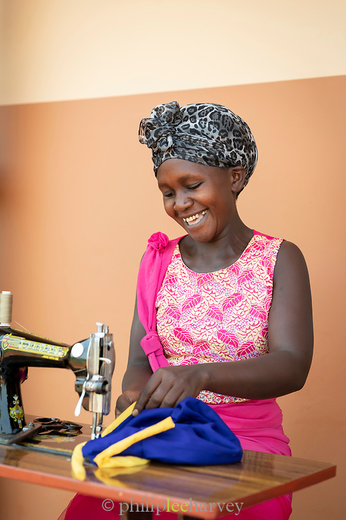 Portrait of woman sewing at Design and Tailoring Centre, Musoto, Uganda