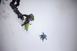 Skiers climbing snowcapped mountain