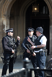 © Licensed to London News Pictures . 27/03/2017 . London , UK . Armed police on duty outside the Houses of Parliament in Westminster . Tributes have been left in response to Khalid Masood's terrorist attack and the killing of PC Keith Palmer . Photo credit: Joel Goodman/LNP