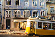 Typical Lisbon trams passing in front of a building with facade covered in ceramic tiles, in Calçada do Combro, near Bairro Alto and Bica districts.