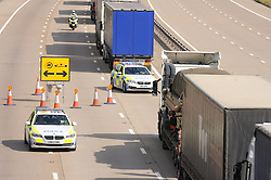 © Licensed to London News Pictures. 30/07/2015 <br /> Police supervision moving the lorries forward.<br /> Lorries stacked up between J8 and J9 M20 (this afternoon 30.07.2015).coast bound.<br /> Traffic misery continues on the M20 with Operation Stack and will most likely remain in place into the weekend.<br /> A 23-mile stretch of the coast-bound carriageway is shut with part of the London-bound side also closed.<br /> <br /> <br /> (Byline:Grant Falvey/LNP)