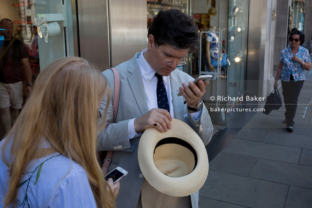 A gentleman checks his messages after removing his summer hat, on 5th July 2017, in London, England.