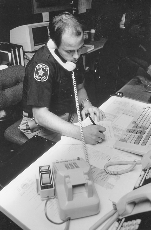 ©1991 Travis County Sheriff's officer takes a report by phone, Austin, Texas