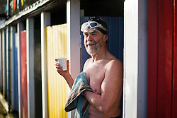 ©  London News Pictures. 26/01/2013. London, UK. A competitor in the Cold Water Swimming Championships at Tooting Bec Lido in South London resting after competing in the biannual event in which some competitors dress in costume. Photo credit: Ben Cawthra/LNP