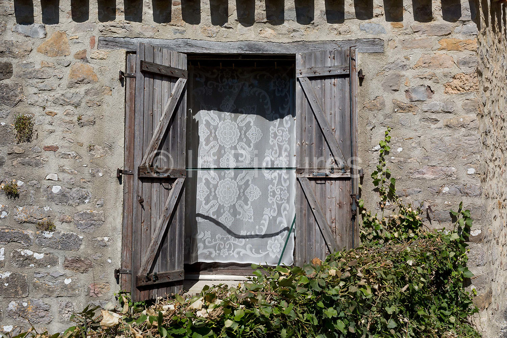Open wooden shutters and traditional lace curtains in the window of a house, on 24th May, 2017, in Ribaute, Languedoc-Rousillon, south of France.