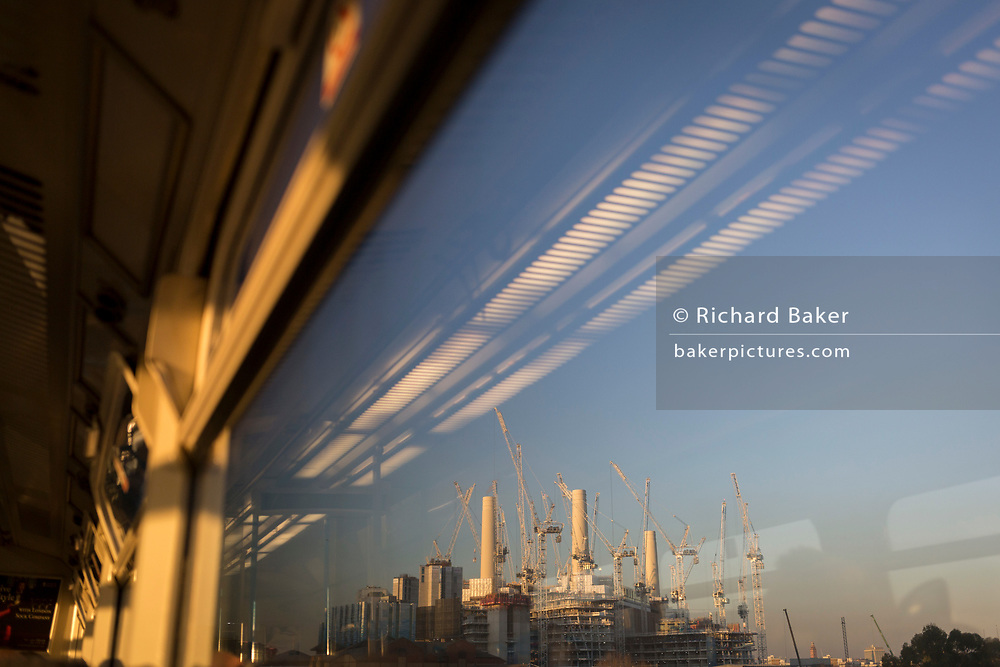 Seen from the window seat of a train carriage that is travelling towards Victoria station, is a landscape of cranes and gantries at the large Battersea Power Station construction site, in London, England, on 4th December 2019.