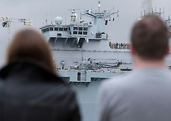 © Licensed to London News Pictures. 04/05/2012. LONDON, UK. Members of the public watch HMS Ocean, the Royal Navy's helicopter carrier, after she made her way up the Thames to moor in Greenwich, London, today (04/05/12). HMS Ocean has been deployed as part of an exercise involving the RAF, British Army and Royal Navy taking place across London as part of security preparations for the 2012 London Olympic Games. Photo credit: Matt Cetti-Roberts/LNP