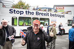 "© Licensed to London News Pictures . 22/09/2018. Bolton, UK. A man wearing a Make Britain Great Again hat and waving a Union Flag poses by the Believe in Britain bus outside the stadium . Pro Brexit campaign group Leave Means Leave host a "" Save Brexit "" and "" Chuck Chequers "" rally at the University of Bolton Stadium , attended by leave-supporting politicians from a cross section of parties , including Conservative David Davis , former UKIP leader Nigel Farage and Labour's Kate Hoey . Photo credit: Joel Goodman/LNP"