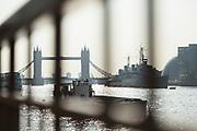 Tower Bridge and HMS Belfast photographed through railings at sunrise