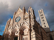 The decorated facade and bell tower of the Duomo di Siena, the Cathedral of Siena, a Roman Catholic church in Siena, Tuscany, Italy