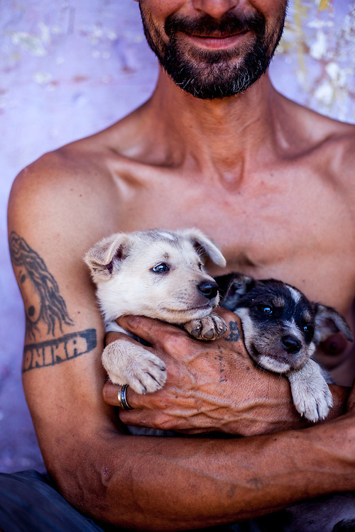"Ladco with two newborn puppies in his arms - he lives at the Roma settlement ""Budulovska Street"" located close to Moldava nad Bodvou in eastern Slovakia. The city has roughly 11200 inhabitants, about 1980 (18%) of them have Roma ethnicity and around 800 are living at the segregated settlement 'Budulovska Street' (2014)."