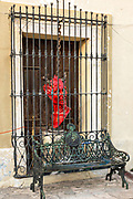 A sculpture of the devil and bench decorate a colonial style building in the Barrio Antiguo or Spanish Quarter neighborhood adjacent to the Macroplaza Grand Plaza in Monterrey, Nuevo Leon, Mexico.
