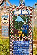 Tombstone showing a logger chopping trees, The  Merry Cemetery ( Cimitirul Vesel ),  Săpânţa, Maramares, Northern Transylvania, Romania.  The naive folk art style of the tombstones created by woodcarver  Stan Ioan Pătraş (1909 - 1977) who created in his lifetime over 700 colourfully painted wooden tombstones with small relief portrait carvings of the deceased or with scenes depicting them at work or play or surprisingly showing the violent accident that killed them. Each tombstone has an inscription about the person, sometimes a light hearted  limerick in Romanian. .<br /> <br /> Visit our ROMANIA HISTORIC PLACXES PHOTO COLLECTIONS for more photos to download or buy as wall art prints https://funkystock.photoshelter.com/gallery-collection/Pictures-Images-of-Romania-Photos-of-Romanian-Historic-Landmark-Sites/C00001TITiQwAdS8