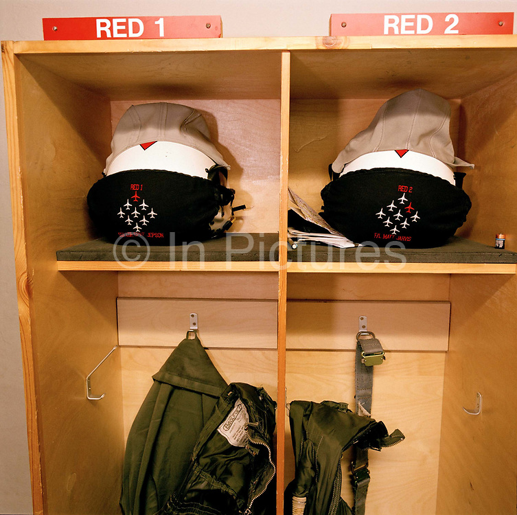 Stored in their respective wooden boxes are the flying helmets and miscellaneous equipment belonging to two pilots of the elite 'Red Arrows', Britain's prestigious Royal Air Force aerobatic team, at their headquarters RAF Scampton, Lincolnshire. All ten pilots have their own storage space for gear. We see the place names of Reds One and Two: Squadron Leader Spike Jepson and Flight Lieutenant Matt Jarvis, whose visors are protected by soft cloths preventing scratches protective face screen. Squadron Leader Jepson is team leader and Flight Lieutenant Jarvis flies slightly behind and to the right in the Red Arrows Diamond Nine formation. On an average winter training day at Scampton, the crews will collect their kit up to six times a day in readiness for the forthcoming summer air show season. Flight Lieutenant Jarvis died of cancer one year later in March 2005.