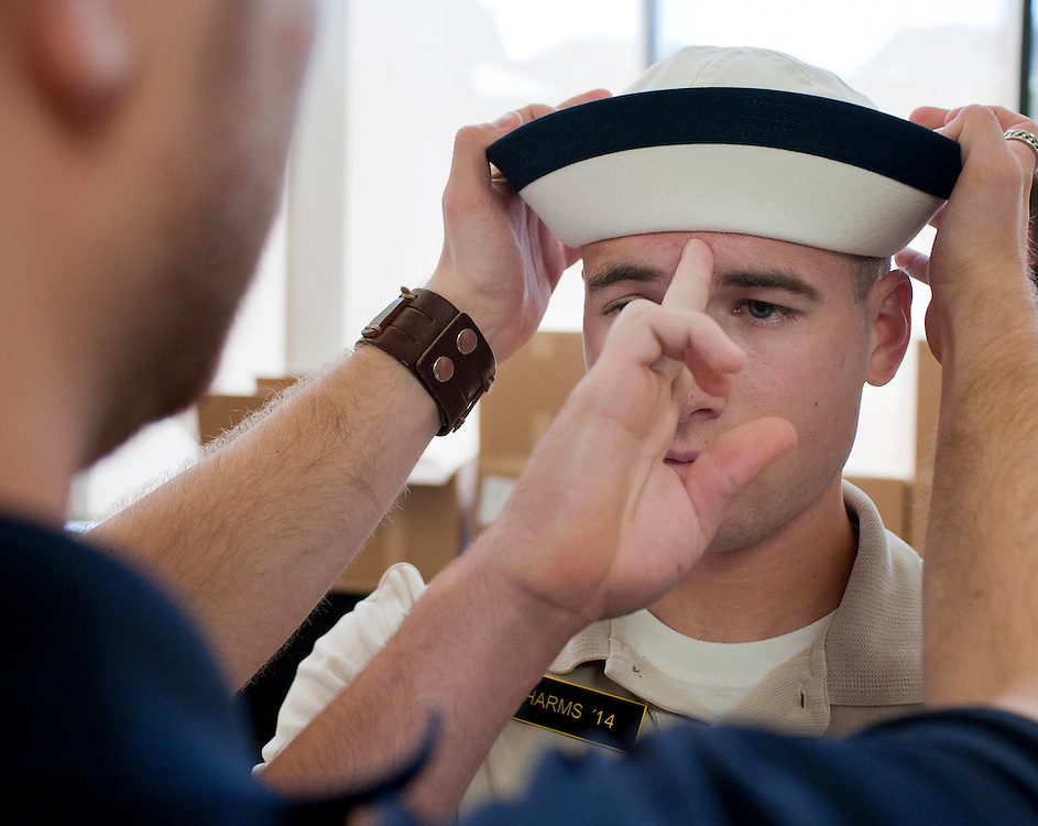 """A freshman is fitted for his """"cover"""" during his processing on his first day at the U.S. Naval Academy in Annapolis, MD. Approximately 1,230 young men and women arrived at the U.S. Naval Academy's Alumni Hall, Thursday, July 1, for Induction Day to begin their new lives as """"plebes"""" or midshipmen fourth class (freshmen). """"I-Day"""" culminates when the members of the Class of 2014 take the oath of office at a ceremony at 6 p.m. in Tecumseh Court, the historic courtyard of the Bancroft Hall dormitory. Over 17,400 young men and women applied to be members of the Naval Academy Class of 2014 - a record for USNA."""