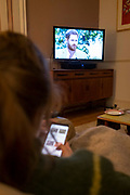 Seen from the rear, a young woman looks at the screen on her phone while watching the Duke and Duchess of Sussexs controversial TV interview with US chat show queen, Oprah, broadcast in ITV in the UK, on 8th March 2021, in London, England. The cntroversial interview accused members of the Britains royal family of racism, forcing the couple to cease official duties and relinquishing their royal titles.